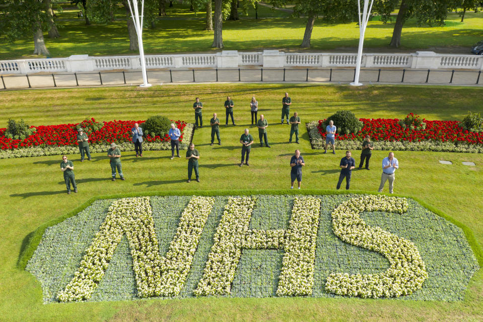 Royal Parks staff applaud the NHS's 72 birthday behind one of two specially created 12 x 5 metre flowerbeds in front of Buckingham Palace in the Memorial Gardens in St James's Park. The letters are made up of 1,500 Begonia semperflorens 'Heaven White' plants in each bed, while the background is 21,000 plants of Echeveria imbricate, Senecio serpens and Sedum pachyclados.