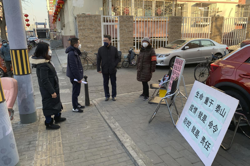 People in face masks stand near a stall to register residents who have recently returned from other provinces in a neighborhood in Beijing, Friday, Jan. 31, 2020. As China institutes the largest quarantine in human history, locking down more than 50 million people in the center of the country, those who have recently been to Wuhan are being tracked, monitored, turned away from hotels and shoved into isolation at their homes and in makeshift quarantine facilities.  (AP Photo/Dake Kang)