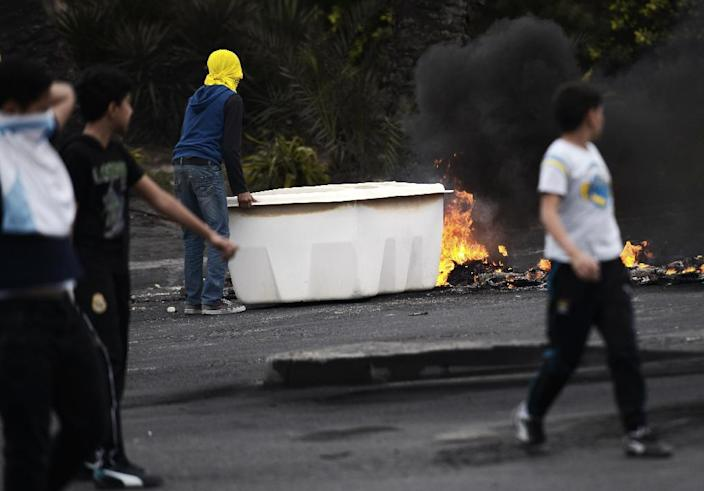 Bahraini protesters block the road during clashes with police following a demonstration to mark the fourth anniversary of the Arab Spring-inspired uprising on February 14, 2015, in Daih, on the outskirts of Manama (AFP Photo/Mohammed al-Shaikh)