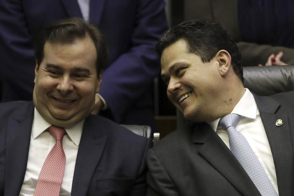 Brazil's Lower House's President Rodrigo Maia, left, and Senate leader David Alcolumbre, share a light moment during the opening of the new legislature at the National Congress, in Brasilia, Brazil, Monday, Feb. 4, 2019. (AP Photo/Eraldo Peres)