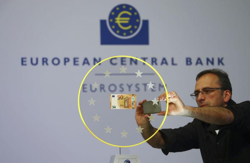 A journalist takes a picture of the new 50 Euro banknote at the ECB headquarters in Frankfurt