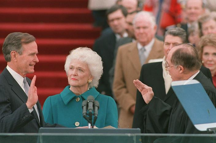 <p>President George Bush raises his right hand as he is sworn in to office as the 41st president of the United States by Chief Justice William Rehnquist outside the Capitol on Jan. 20, 1989. First lady Barbara Bush holds the Bible for her husband. Former President Reagan is in the background. (Photo: Bob Daugherty/AP) </p>