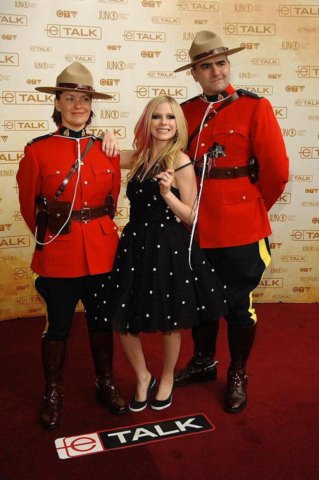 """Avril Lavigne poses with two mounties as she arrives at the Juno Awards in Calgary, Alberta, Canada. The pop-punk princess was all smiles early in the evening, but her excitement faded when she wound up trophy-less. George Pimentel/<a href=""""http://www.wireimage.com"""" target=""""new"""">WireImage.com</a> - April 6, 2008"""