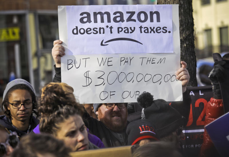 FILE - In this Wednesday, Nov. 14, 2018, file photo, protesters hold up anti-Amazon signs during a coalition rally and news conference of elected officials, community organizations and unions opposing the second Amazon headquarters getting subsidies to locate in Long Island City, in New York. Amid growing concern about the incentives that cities promised Amazon to land its new headquarters, Kentucky lawmakers considered a bill in 2019 to keep the details of Louisville's failed pitch to the retailer forever secret. (AP Photo/Bebeto Matthews, File)