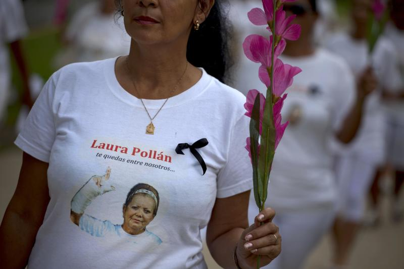 """A member of Cuba's Ladies in White dissident group, wearing a T-shirt with an image of the late co-founder of the group, Laura Pollan, participates in a march marking one year since the death of Pollan in Havana, Cuba, Sunday, Oct 14, 2012. The Ladies in White was formed in 2003 mostly by wives and family members of 75 dissidents jailed in a crackdown on dissent. Pollan had been married to one of the dissident prisoners, Hector Maseda. The T-shirt reads in Spanish """"you stay with us."""" (AP Photo/Ramon Espinosa)"""
