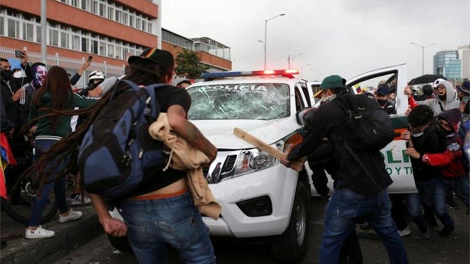 """Demonstrators hit a police vehicle during a protest against the tax reform of President Ivan Duque""""s government in Bogota, Colombia April 28, 2021."""