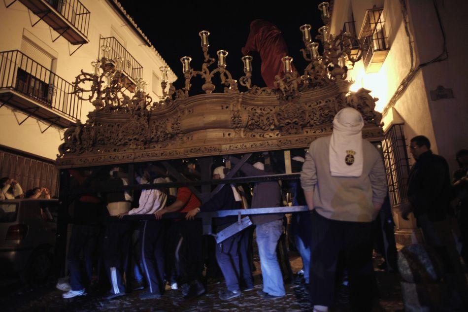 "Members of the Nuestro Padre Jesus Nazareno brotherhood known as ""costaleros"" carry a weighted structure for Christ, traditionally known as ""paso"", from their brotherhood house to a church for the upcoming Holy Week processions in Ronda near Malaga, southern Spain."