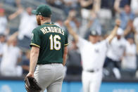Oakland Athletics relief pitcher Liam Hendriks (16) leaves the mound as New York Yankees' third base coach Phil Nevin celebrates, right, after the Yankees' Mike Ford hit a pinch-hit, walk-off, solo home run in the ninth inning of a baseball game, Sunday, Sept. 1, 2019, in New York. (AP Photo/Kathy Willens)