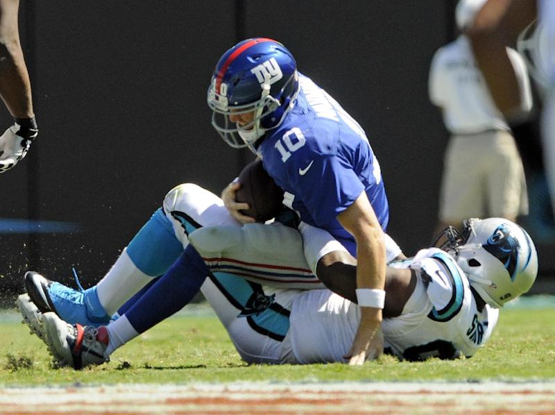 New York Giants' Eli Manning (10) is sacked by Carolina Panthers' Kawann Short during the first half of an NFL football game in Charlotte, N.C., Sunday, Sept. 22, 2013. (AP Photo/Mike McCarn)