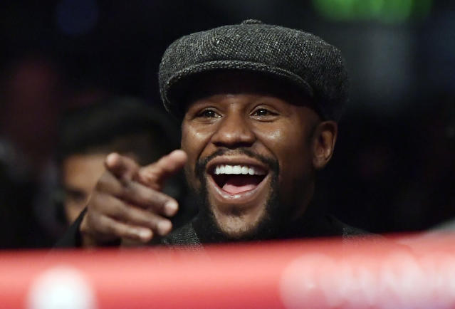 Boxer Floyd Mayweather points to someone in the crowd as he watches a boxing match between Deontay Wilder and Tyson Fury, of England, for the WBC heavyweight championship, Saturday, Dec. 1, 2018, in Los Angeles. (AP Photo/Mark J. Terrill)
