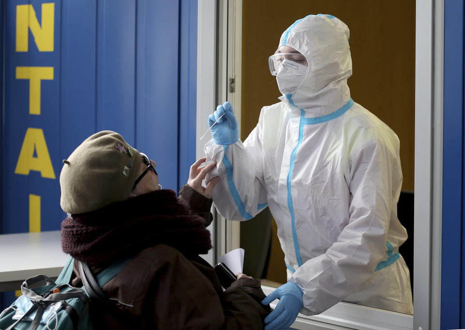 A medical worker, right, tries to test woman for COVID-19 in a set up for rapid new coronavirus testing in Vienna, Austria, Monday, Nov. 30, 2020. The Austrian government has moved to restrict freedom of movement for people, in an effort to slow the onset of the COVID-19 disease and the spread of the coronavirus. (AP Photo/Ronald Zak)