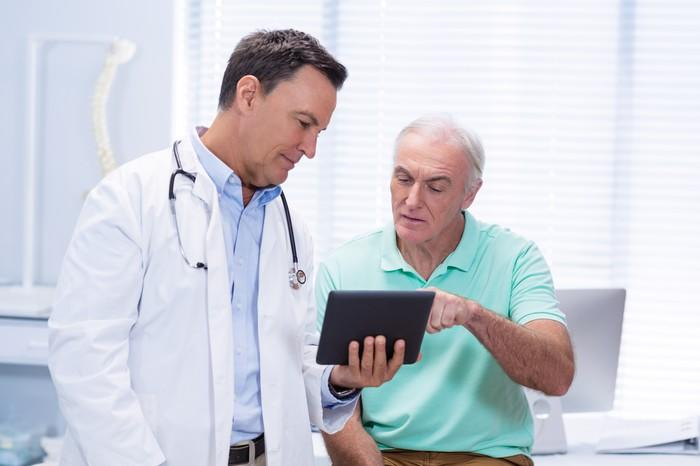 A doctor and patient review information on a tablet in an exam room.