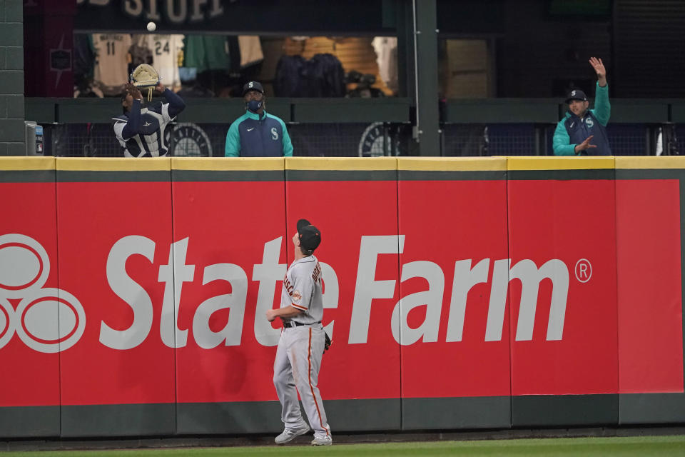 San Francisco Giants left fielder Alex Dickerson watches as Seattle Mariners bullpen catcher Fleming Baez, left, catches a solo home run hit by Mitch Haniger during the seventh inning of a baseball game Saturday, April 3, 2021, in Seattle. (AP Photo/Ted S. Warren)