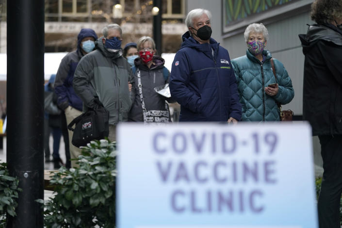 People stand near a sign as they wait in line to receive the first of two doses of the Pfizer vaccine for COVID-19, Sunday, Jan. 24, 2021, at a one-day vaccination clinic set up in an Amazon.com facility in Seattle and operated by Virginia Mason Franciscan Health. (AP Photo/Ted S. Warren)