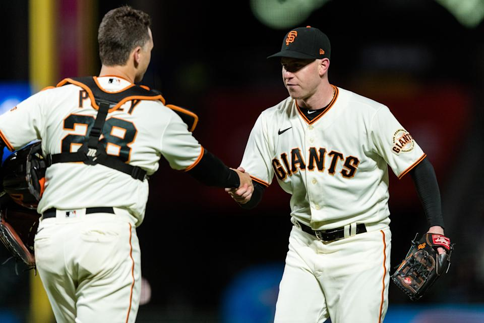 Anthony DeSclafani celebrates with catcher Buster Posey after pitching a shutout against the Rockies.