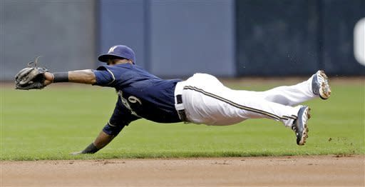 Milwaukee Brewers shortstop Jean Segura makes a diving catch on a ball hit by Texas Rangers' Ian Kinsler during the first inning of a baseball game Wednesday, May 8, 2013, in Milwaukee. (AP Photo/Morry Gash)