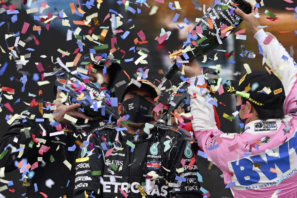 FILE - In this Nov. 15, 2020, file photo, driver Sergio Perez of Mexico, right, pours champagne on winner Mercedes driver Lewis Hamilton of Britain on the podium of the Formula One Turkish Grand Prix at the Istanbul Park circuit racetrack in Istanbul. (Ozan Kose/Pool via AP, File)