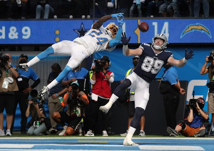 Chargers' Nasir Adderley leaps in the air to break up a potential TD pass to Dallas Cowboys' Blake Jarwin.