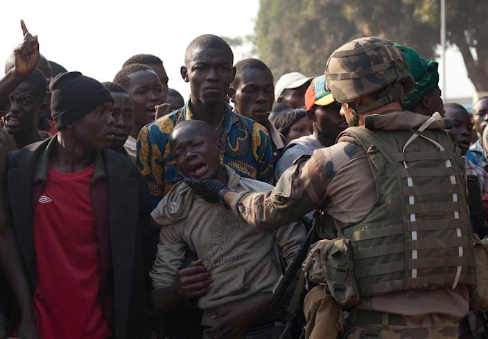 A French soldier tries to calm a hysterical boy, after at least two young men were wounded by passing Chadian troops, during a protest outside Mpoko Airport in Bangui, Central African Republic, Monday, Dec. 23, 2013. Hundreds of demonstrators gathered at the entrance to the airport Monday morning carrying signs protesting Chadian forces and expressing support for French troops and other regional African forces. At least two people were wounded as pickups of Chadian soldiers sped through the gathered crowd firing off several rounds.(AP Photo/Rebecca Blackwell)