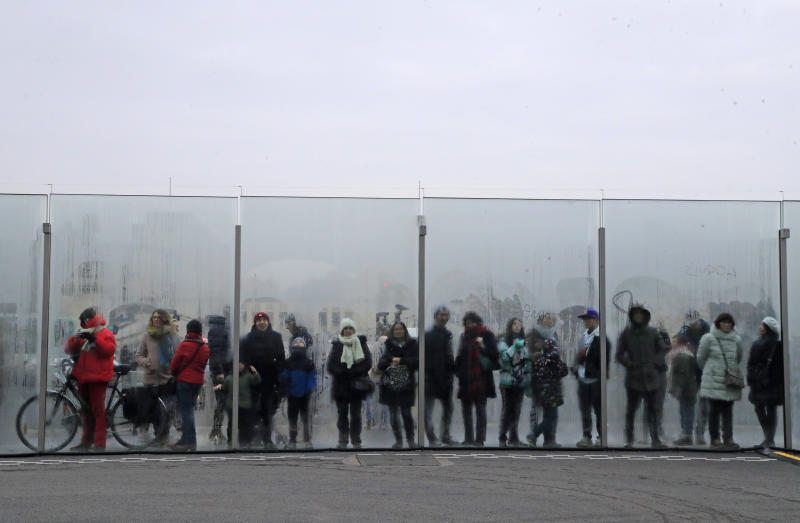 """People watch through the security bulletproof glass barrier at the Eiffel Tower in Paris, Saturday Jan. 25, 2020, the dance performance who marks the Chinese New Year. This year marks the """"Year of the Rat"""" in the Chinese Lunar calendar. (AP Photo/Michel Euler)"""