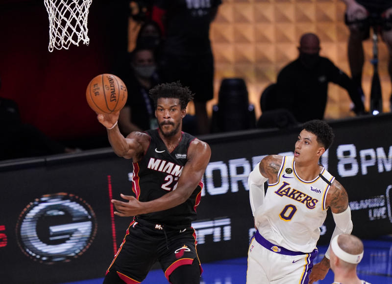 Miami Heat's Jimmy Butler (22) passes the ball against Los Angeles Lakers' Kyle Kuzma (0) during the first half in Game 3 of basketball's NBA Finals, Sunday, Oct. 4, 2020, in Lake Buena Vista, Fla. (AP Photo/Mark J. Terrill)