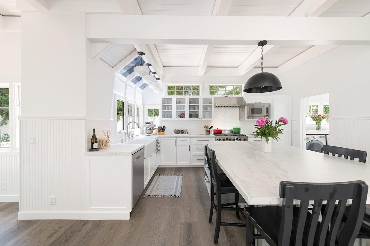 <p>The kitchen is bright and airy, making it the perfect spot for someone who loves to cook and entertain. Lots of texture, thanks to the wainscotting on the walls and the wood paneled ceiling, keep the white kitchen from feeling cold, while giving a subtle nod to modern farmhouse style. A farmhouse sink and glass-front cabinets only add to the room's charms. </p>