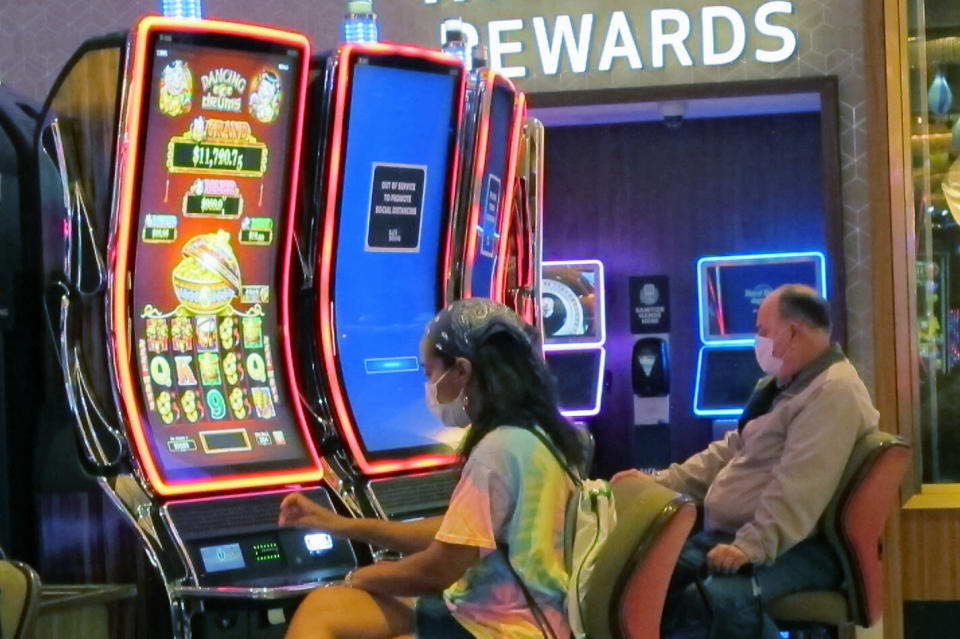 Gamblers wear face masks while playing slot machines at the Hard Rock casino in Atlantic City, N.J., on July 2, 2020, the first day it reopened after being closed for four months due to the coronavirus outbreak. American Gaming Association President Bill Miller said Tuesday, Oct. 27, 2020, the industry is adapting to the pandemic but needs assistance from the government for its casinos and workers. (AP Photo/Wayne Parry)