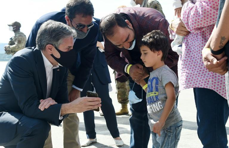 US Secretary of State Antony Blinken shows a picture of his children to a young Afghan refugee during evacuation operations at Ramstein Air Base in Germany (AFP/Olivier DOULIERY)