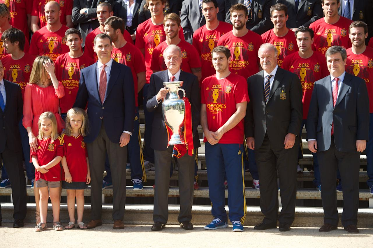 MADRID, SPAIN - JULY 02:  King Juan Carlos I of Spain holds the UEFA EURO 2012 trophy next to (L-R) Princess Letizia of Spain, Princess Leonor of Spain, Princess Sofia of Spain, Prince Felipe of Spain, Iker Casillas of Spain and head coach Vicente del Bosque and members of the Spain's victorious national football team at the Zarzuela Palace on July 2, 2012 in Madrid, Spain.  (Photo by Pool/Getty Images)