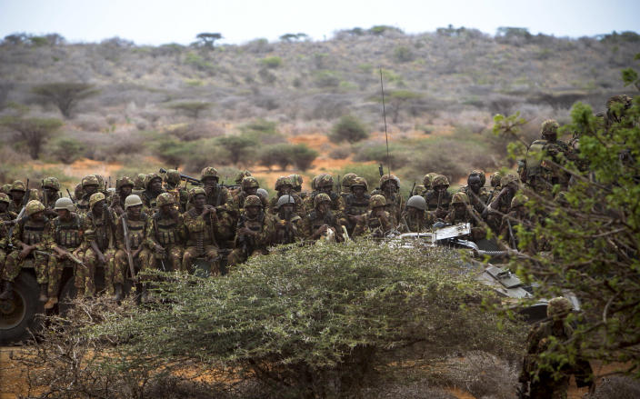 In this photo released by the African Union-United Nations Information Support Team, Kenyan soldiers serving with the African Union Mission in Somalia (AMISOM) sit on a flat-bed truck as a convoy makes its way between the port and the airport in Kismayo, southern Somalia, Tuesday, Oct. 2, 2012. Allied African troops have taken full control of Kismayo in Somalia, the last stronghold of al-Shabab Islamist rebels who have been fighting against the country's internationally backed government, a Kenyan military official said Tuesday, and Kenya Defence Forces and the Somali National Army are now patrolling the streets. (AP Photo/AU-UN IST, Stuart Price)