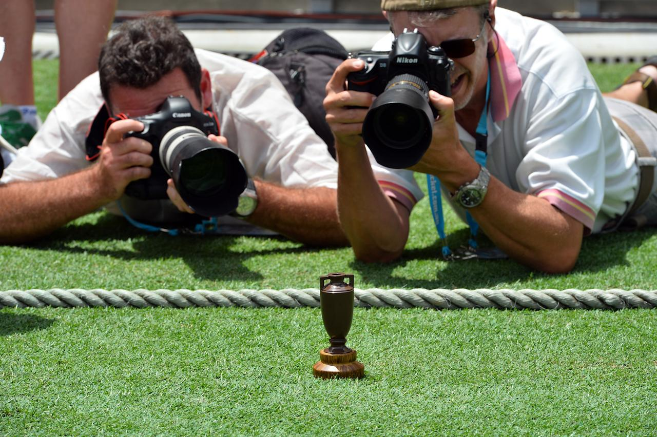 Photographers take pictures of the Ashes Urn at the Gabba in Brisbane on November 20, 2013 on the eve of the first Ashes cricket Test match between England and Australia.      AFP PHOTO / Saeed KHAN  IMAGE RESTRICTED TO EDITORIAL USE - STRICTLY NO COMMERCIAL USE        (Photo credit should read SAEED KHAN/AFP/Getty Images)