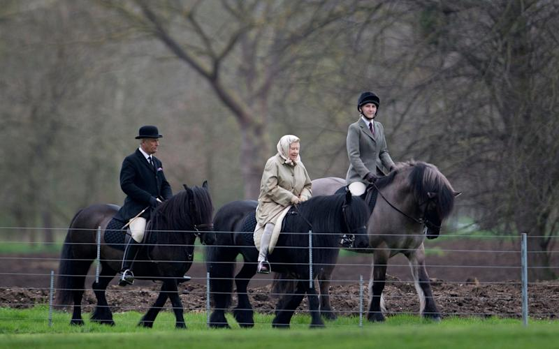 The monarch, 90, was spotted dressed in a beige coat and matching shawl, which she tied round her head, as she rode the small black horse alongside two others - Kelvin Bruce