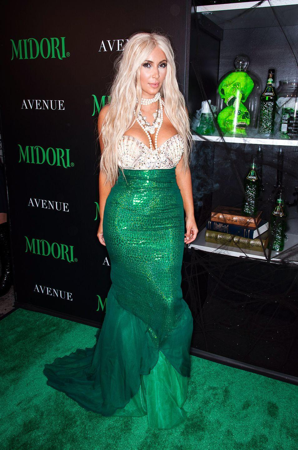 <p>Mermaids have never looked so glam! With a string of pearls, a shell bra, and dramatic green skirt, a blonde Kim shined on the *green* Halloween carpet. </p>