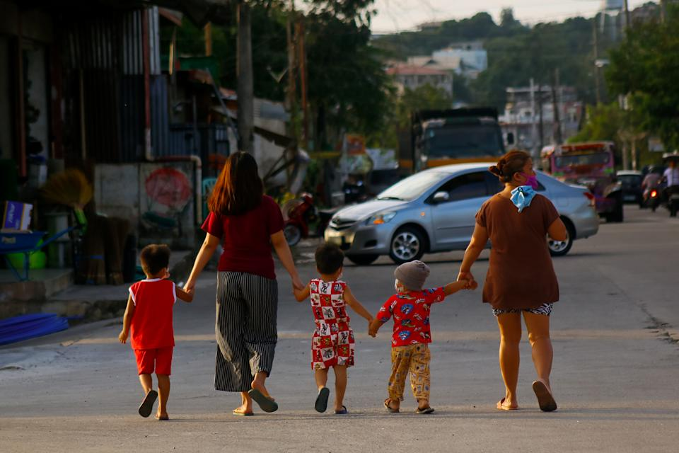 A kids walking with the guidance of adult women are seen in the boundary of Antipolo-Angono, Rizal, Philippines on January 16, 2021. (Photo: Ryan Eduard Benaid/NurPhoto via Getty Images)