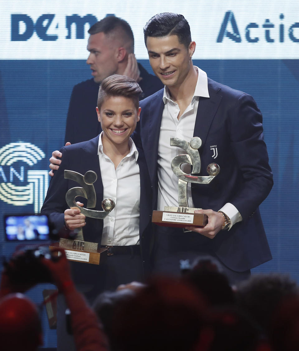Juventus' Cristiano Ronaldo, right, and Manuela Giugliano pose with the trophy for best Italian Serie A player, during the Gran Gala' soccer awards ceremony, in Milan, Italy, Monday, Dec. 2, 2019. (AP Photo/Antonio Calanni)