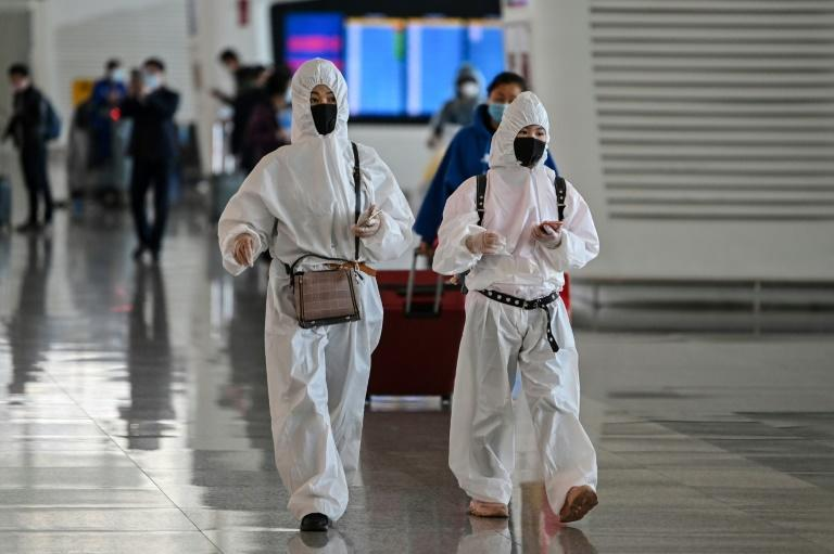 Passengers in protective gear walk through Tianhe Airport after it was reopened in Wuhan in China's central Hubei province