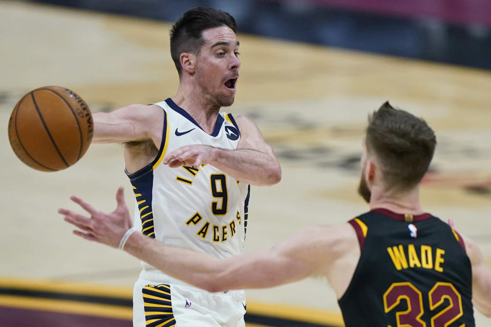 Indiana Pacers' T.J. McConnell (9) passes the ball away from Cleveland Cavaliers' Dean Wade (32) during the second half of an NBA basketball game, Wednesday, March 3, 2021, in Cleveland. (AP Photo/Tony Dejak)
