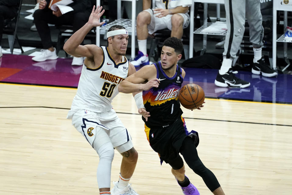 Phoenix Suns guard Devin Booker (1) drives as Denver Nuggets forward Aaron Gordon (50) defends during the second half of Game 1 of an NBA basketball second-round playoff series, Monday, June 7, 2021, in Phoenix. (AP Photo/Matt York)