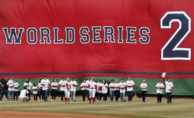 Boston Marathon bombing victims and family members walk in from left field during pre-game ceremonies before a baseball game between the Boston Red Sox and the Milwaukee Brewers on Opening Day at Fenway Park in Boston, Friday, April 4, 2014. (AP Photo/Michael Dwyer)