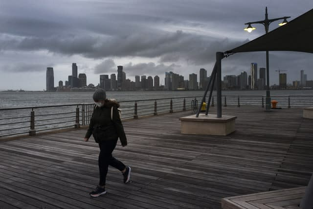 A woman wears a face mask as she walks on Pier 45 in Hudson River Park, New York (AP)