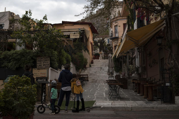 A family looks at an empty street in the Plaka district of Athens during a lockdown order by the Greek government to prevent the spread of the coronavirus in Athens, on Tuesday, April 14, 2020. Outbreaks of COVID-19 prompted Greece to impose two countrywide lockdowns, in the spring, keeping infection rates low, and in the fall as authorities scrambled to cope with a rampant rise in cases. (AP Photo/Petros Giannakouris)