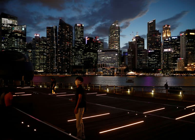 A man wearing a mask in precaution of the coronavirus looks on along the Marina Bay Waterfront Promenade in Singapore