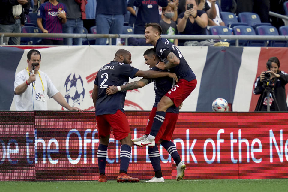 New England Revolution forward Gustavo Bou, center, is congratulated by teammates Andrew Farrell (2) and Arnor Ingvi Traustason after scoring a goal against CF Montreal during the first half of an MLS soccer match, Sunday, July 25, 2021, in Foxborough, Mass. (AP Photo/Mary Schwalm)