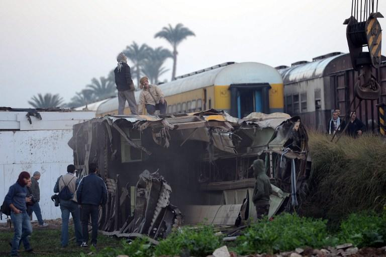 EGYPT, Cairo : People inspect at the wreckage of a train in the Giza in Badrashin, about 40 km west of Cairo, on January 15, 2013, at least 19 people where killed and injured 105. The train carrying conscripts from south Egypt to Cairo derailed in the Giza neighbourhood of Badrasheen, state media reported. Giza governor Ali Abdelrahman said emergency services were at the scene and ambulances were ferrying the injured to hospital. The accident is the latest in a string of transport disasters plaguing the country. AFP PHOTO / KHALED DESOUKI