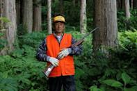 Apple farmer Satomi Ito, 66, holds his hunting rifle as he poses for a photograph in the woods next to a site where his neighbour was mauled by a wild bear last year, in Kitaakita, Akita prefecture, northern Japan June 21, 2018. Picture taken June 21, 2018. REUTERS/Kiyoshi Takenaka