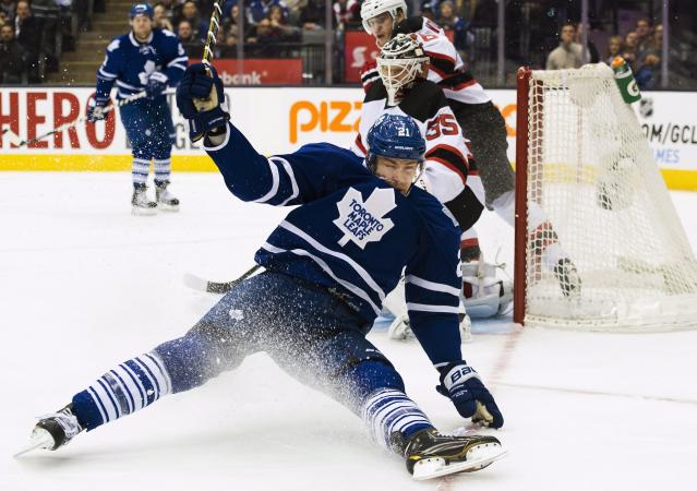 Toronto Maple Leafs forward James van Riemsdyk, front, falls after being tripped up by New Jersey Devils goalie Cory Schneider (35) during second period NHL hockey action in Toronto on Sunday, Jan. 12, 2014. (AP Photo/The Canadian Press, Nathan Denette)