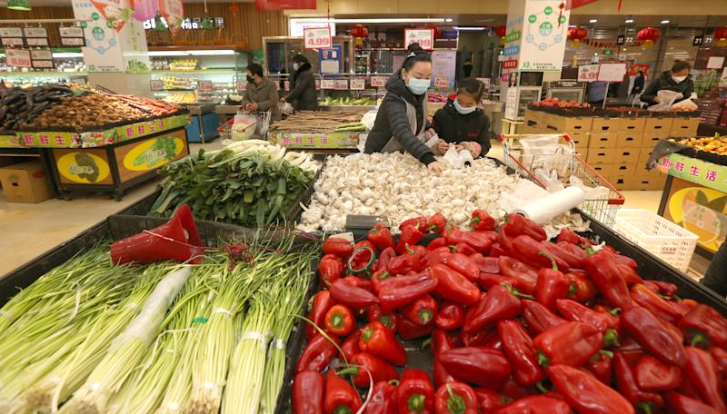 Pictured are Chinese customers in a supermarket vegetable section.