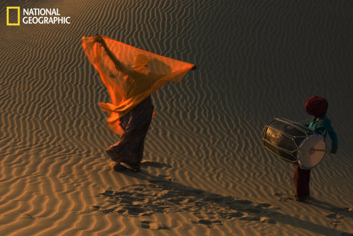 """Like this drummer boy and dancer girl, many more folk musicians come from the nearby village of Khuhri-Jaisalmer and entertain tourists, domestic as well as foreign, on the sand dunes of Thar Desert. Photograph courtesy Shivji Joshi/National Geographic Your Shot. <br> <br> <a href=""""http://ngm.nationalgeographic.com/your-shot/weekly-wrapper"""" rel=""""nofollow noopener"""" target=""""_blank"""" data-ylk=""""slk:Click here"""" class=""""link rapid-noclick-resp"""">Click here</a> to see more photos from National Geographic Your Shot."""