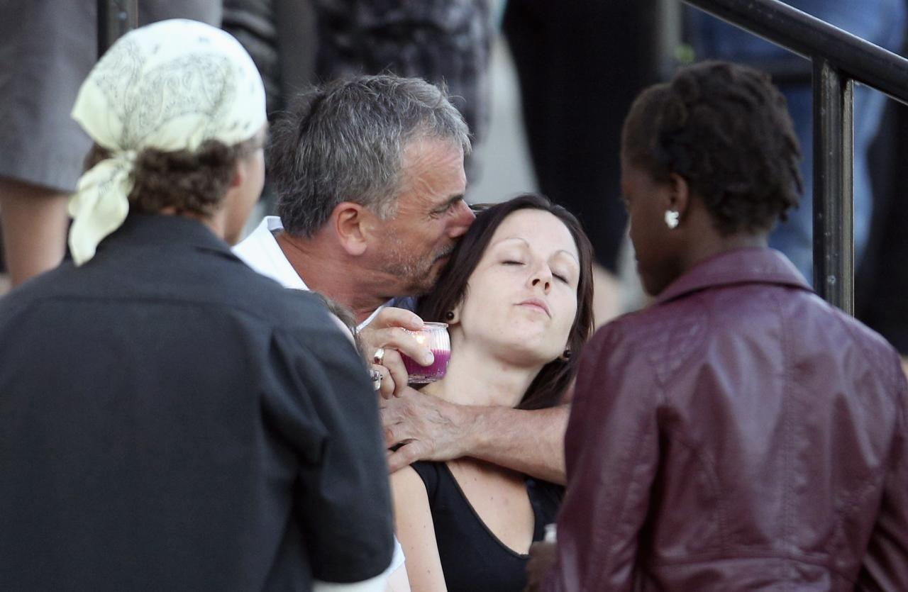A man holds a candle as he hugs a woman during a vigil at the Sainte-Agnes church in Lac-Megantic, Quebec July 12, 2013. Shell-shocked residents of Lac-Megantic took small steps on a long path back to normalcy on Friday as they returned to homes and businesses just a short walk from the lakeside town's center, devastated by a fiery rail crash last week. REUTERS/Mathieu Belanger (CANADA - Tags: DISASTER TRANSPORT SOCIETY)