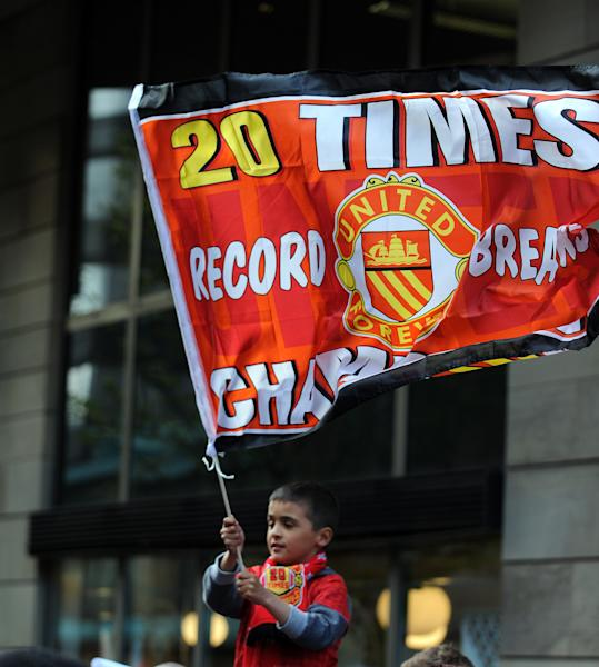 A young Manchester United fan celebrates during the premiership trophy parade at Albert Square in Manchester, England, Monday May 13, 2013. (AP Photo/Clint Hughes)